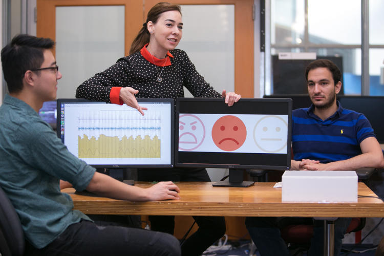 <p>Professor Dina Katabi (middle) explains how PhD Fadel Adib's face (right) is neutral, but that EQ-Radio's analysis of his heartbeat and breathing show that he is sad</p>