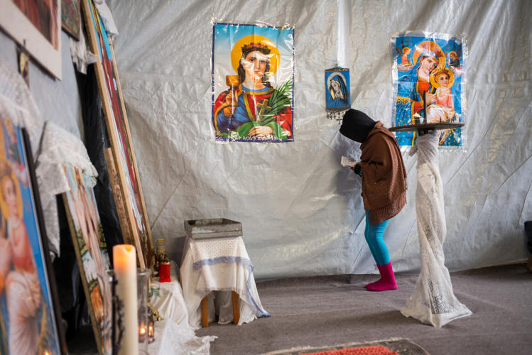 <p>Praying inside the Eritrean church in the south part of the camp (the church wasn't demolished during the evictions).</p>