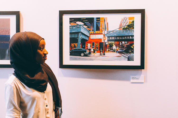<p>A student poses at the &quot;Views From The Block&quot; exhibit (shot by <em>Street Dreams</em> magazine)</p>