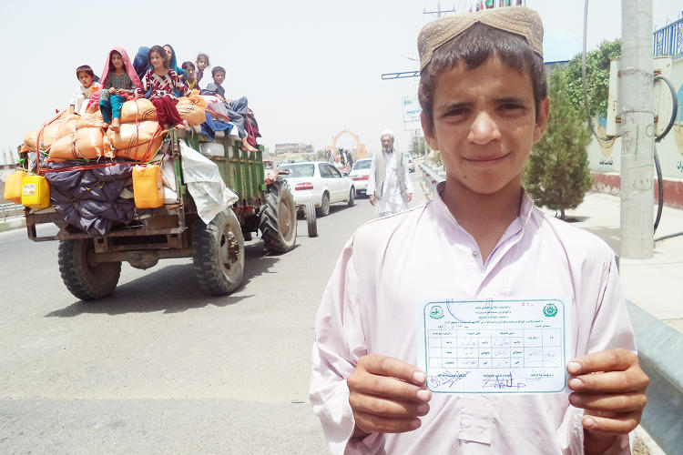 <p>A young Afghan boy in Helmand Province shows the beneficiary documents required to receive IRC cash assistance.</p>